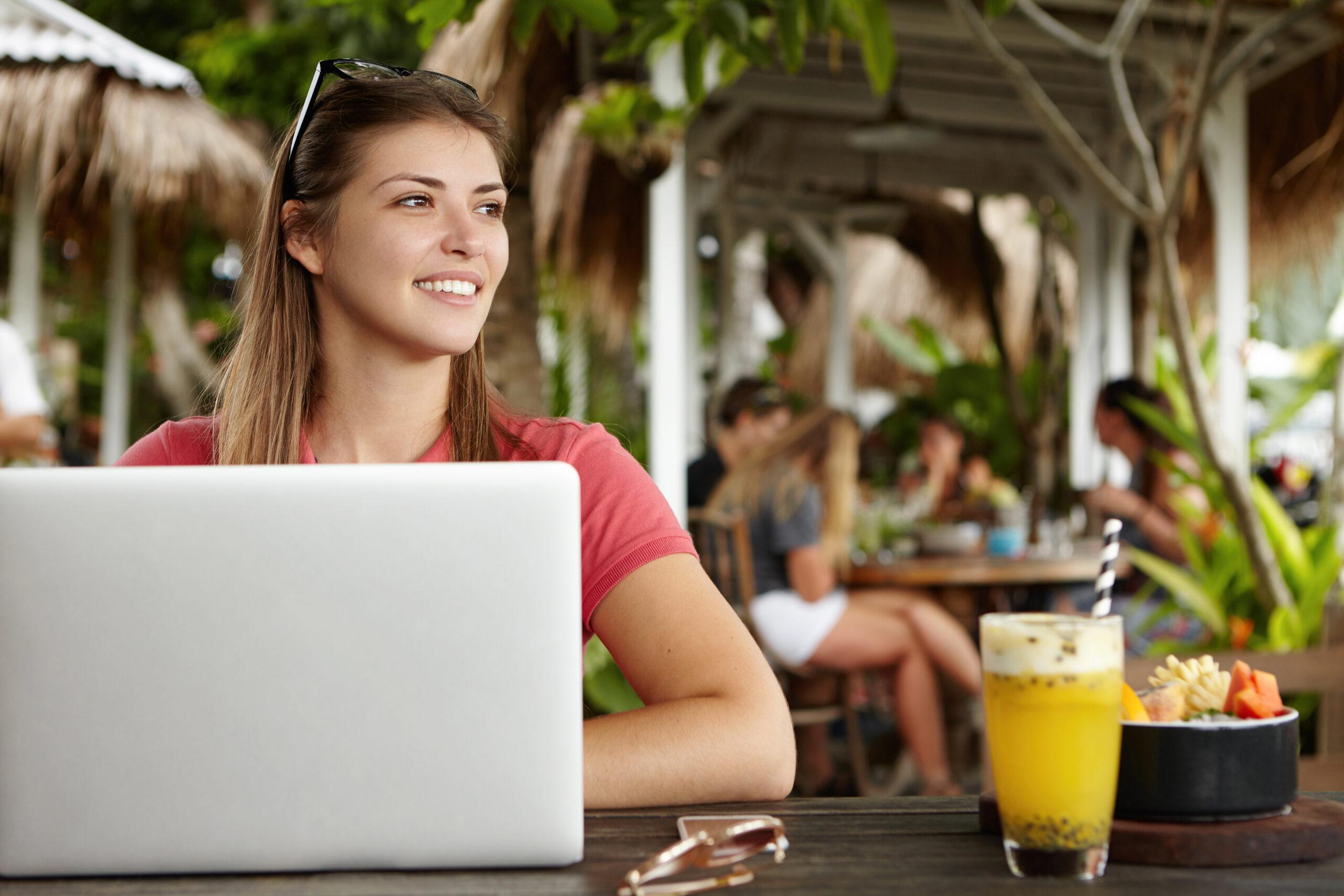 Une femme freelance aux cheveux longs travaillant à distance sur un ordinateur portable moderne, utilisant le wi fi gratuit pendant le petit-déjeuner dans un café, assise à une table en bois avec un verre de smoothie et des fruits.
